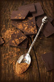 Broken line chocolate bar with a silver spoon — Stock Photo