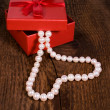 Red gift box with a pearl necklace in the shape of heart — Stock Photo
