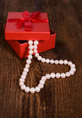 Red gift box with a pearl necklace in the shape of heart — Stockfoto