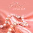 Pearl necklace on a pink silk — Stockfoto