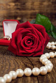 Pearl necklace, red rose and gold ring — Stock Photo