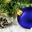 Blue Christmas ball and spruce branches in the snow — Stock Photo