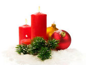 Red candles and fir branches and Christmas balls in snow — Stock Photo