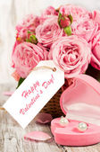 Pink roses and gift in a basket — Stock Photo