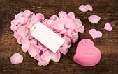 Rose petals in heart shape on wooden — Stock Photo