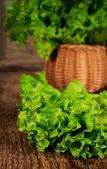 Fresh lettuce leaves in a wicker basket — Stock Photo