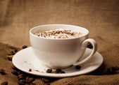 Cappuccino on burlap — Stock Photo