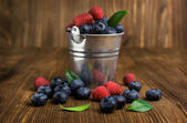 Blueberries and raspberries in a small bucket — Stockfoto