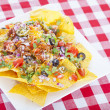 Cheesy Nachos on a Red Checkered Tablecloth — Stock Photo