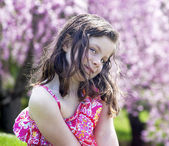 Coy little girl sitting in a garden — Stock Photo