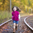 Beautiful little girl running on the train tracks — Stock Photo