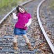 Beautiful girl posing on the train tracks — Stock Photo
