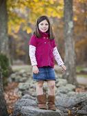 Pretty girl portrait in the park climbing on rocks — Stock Photo