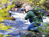 Male photographer taking photos in a waterfall in the Fall — Stock Photo