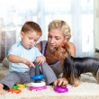 Mother, child boy and pet dog playing together indoor — Stock Photo #10661296