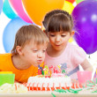 Stock Photo: Kids celebrating birthday party and blowing candles on cake