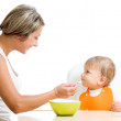 Young mother spoon feeding her cute baby girl isolated on white — Stock Photo