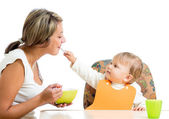 Young mother spoon feeding her playful child girl isolated on wh — Stockfoto