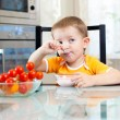 Child boy eating healthy food in kitchen — Stock Photo #12891348