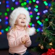 Pretty preschool girl decorating Christmas tree over bright fest — Stock Photo