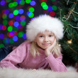 Kid girl dressed in Santa Claus hat lying near Christmas tree wi — Zdjęcie stockowe