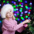 Pretty kid schoolgirl decorating Christmas tree over bright fest — Stock Photo