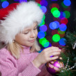 Pretty preschool girl decorating Christmas tree over bright fest — Stock Photo #13164835