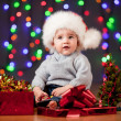 Funny baby in Santa Claus hat on bright festive background — Stock Photo #13164864