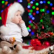 Funny baby in Santa Claus hat on bright festive background — Stock Photo #13164870