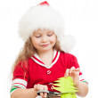 Kid girl in Santa Claus hat cutting christmas tree from paper — Stock Photo