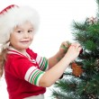 Pretty preschool girl decorating Christmas tree isolated on whit — 图库照片