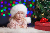 Funny baby in Santa Claus hat on bright festive background — Stok fotoğraf