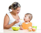 Mother feeding her baby girl by spoon — Stock Photo