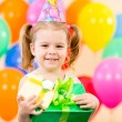 Pretty girl with colorful balloons and gift — Stock Photo #13358420