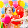 Pretty children with colorful balloons and gifts on birthday par — Stock Photo #13358425