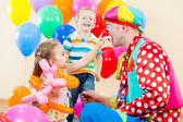 Happy children and clown on birthday party — Stockfoto