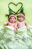 Two twins brothers babies weared in acorn hats — Stock Photo