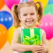 Girl  with colorful balloons and gift — Stockfoto