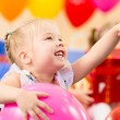 Foto Stock: Joyful kid girl on birthday party