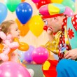 Happy child girl and clown playing on birthday party — Stock Photo #13467528