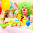 Happy kids with clown on birthday party — Stockfoto