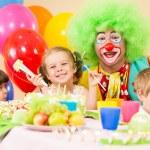 Kids celebrating birthday party with clown — Stock Photo