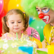 Foto Stock: Happy child girl with clown on birthday party