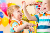 Joyful kids with clown on birthday party — Стоковое фото