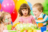 Kids celebrating birthday party and blowing candles on cake — Stok fotoğraf