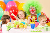 Kids celebrating birthday party with clown — Stock Photo