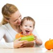 Mother with baby baby at table. Boy holding zucchini — Stock Photo #13470174