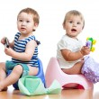 Babies toddlers sitting on chamber pot and playing with toys — Foto de stock #13470379