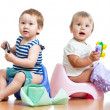 Foto Stock: Babies toddlers sitting on chamber pot and playing with toys