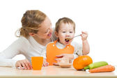 Baby eating vegetables puree by spoon himself and sitting on mot — Stock Photo